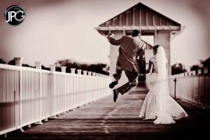 Groom jumps for joy with bride.