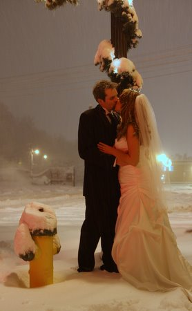Luke and Lindsay kiss in the snow on their wedding day.
